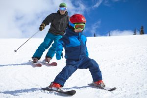 young father and his son enjoying ski vacation.